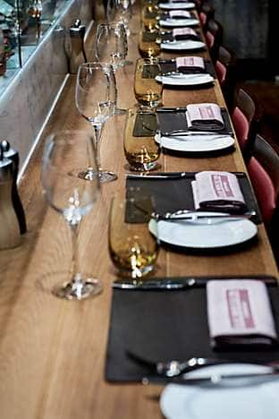 Place settings at the wooden bar in front of the charcuterie counter