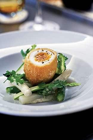 An entrée of asparagus with crispy egg