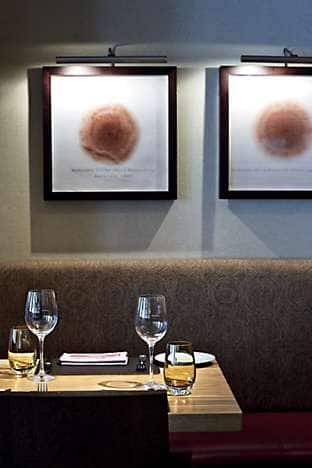 Part of Bar Boulud's dining area. Chef-owner Daniel Boulud chose much of the artwork, such as these Wine Stain pictures by Vik Muniz