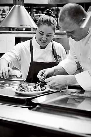 Chef Pratsch plating a dish with one of his team