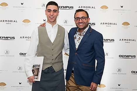 John Nassari (right) and a Mandarin Oriental colleague with the book at the launch party