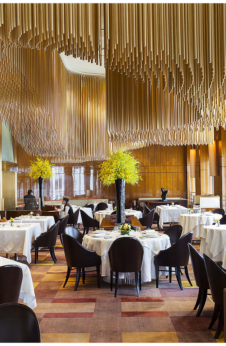 The Adam Tihany-designed interior of Amber with a sculptural ceiling light made of thousands of bronze rods