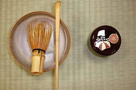 A bamboo whisk, spoon and a lacquer container of green tea