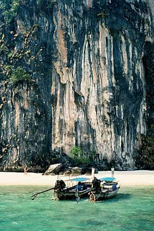 Longtails moor on a secluded beach at the foot of Ao Phang-Nga's limestone cliffs