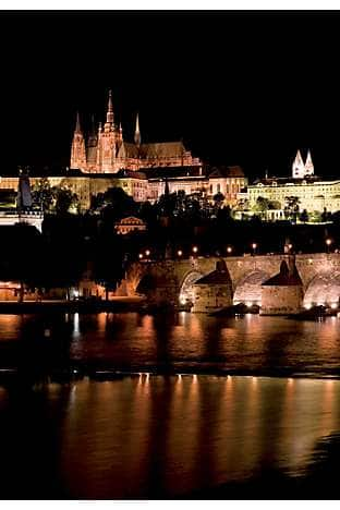 Prague Castle and Hradcany lit up above Malá Strana and Charles Bridge