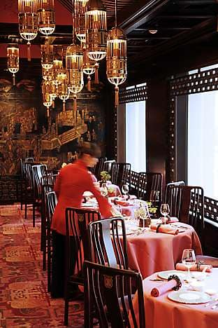 A waitress lays tables in Man Wah, high on the top floor