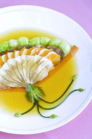 Assorted steamed vegetables are arranged in a familiar fan shape