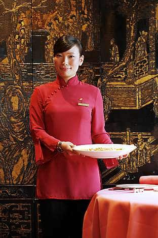 A waitress in Man Wah wears a uniform inspired by traditional costume