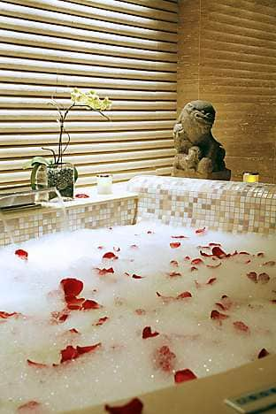 Rose petals scattered on a bath in the Koku treatment room