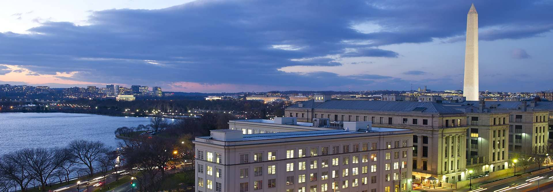 Panoramic view of the Mandarin Oriental, Washington DC and Washington Monument lit up at night.