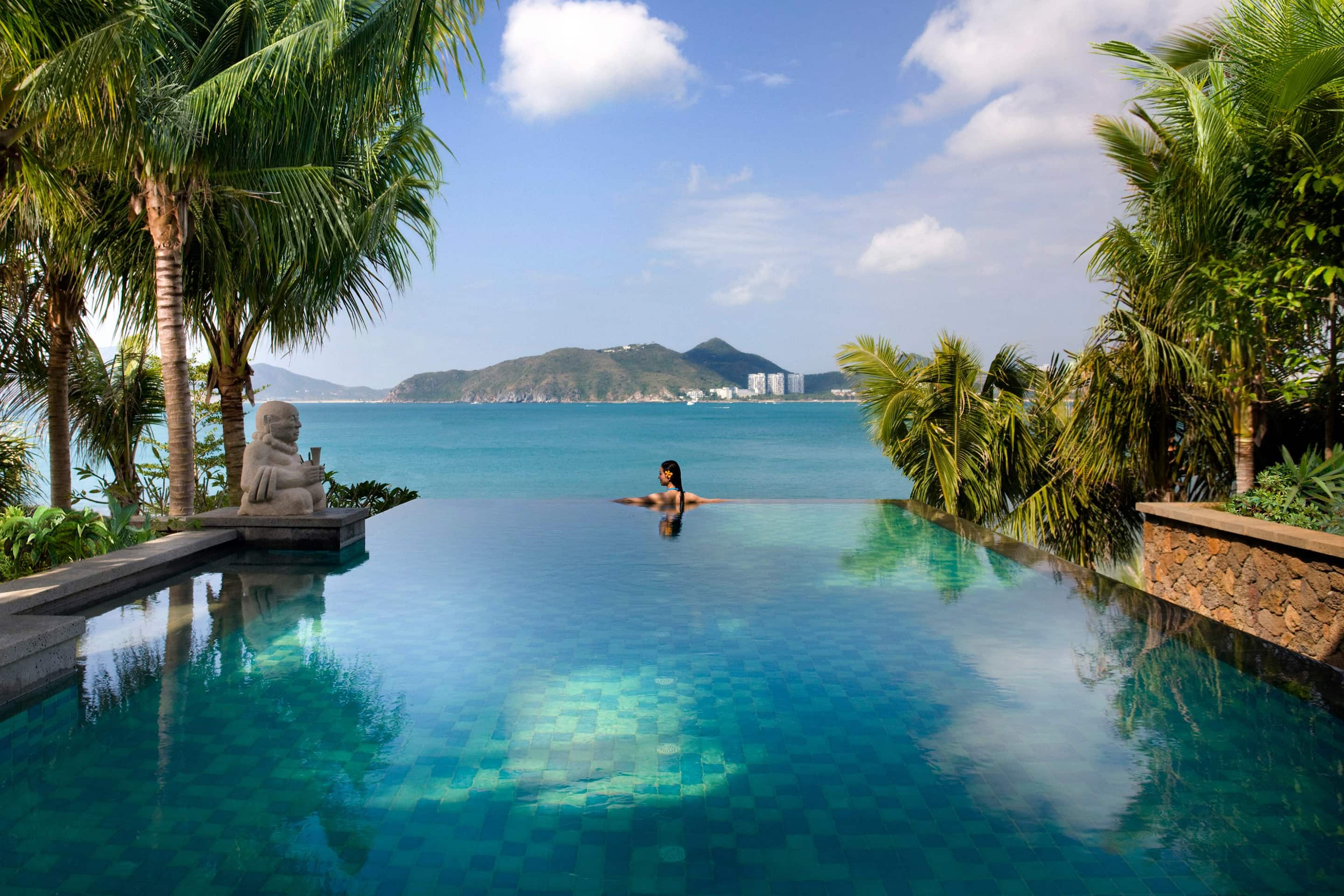 Woman looking out onto the ocean from the palm-fringed infinity pool at Mandarin Oriental, Sanya