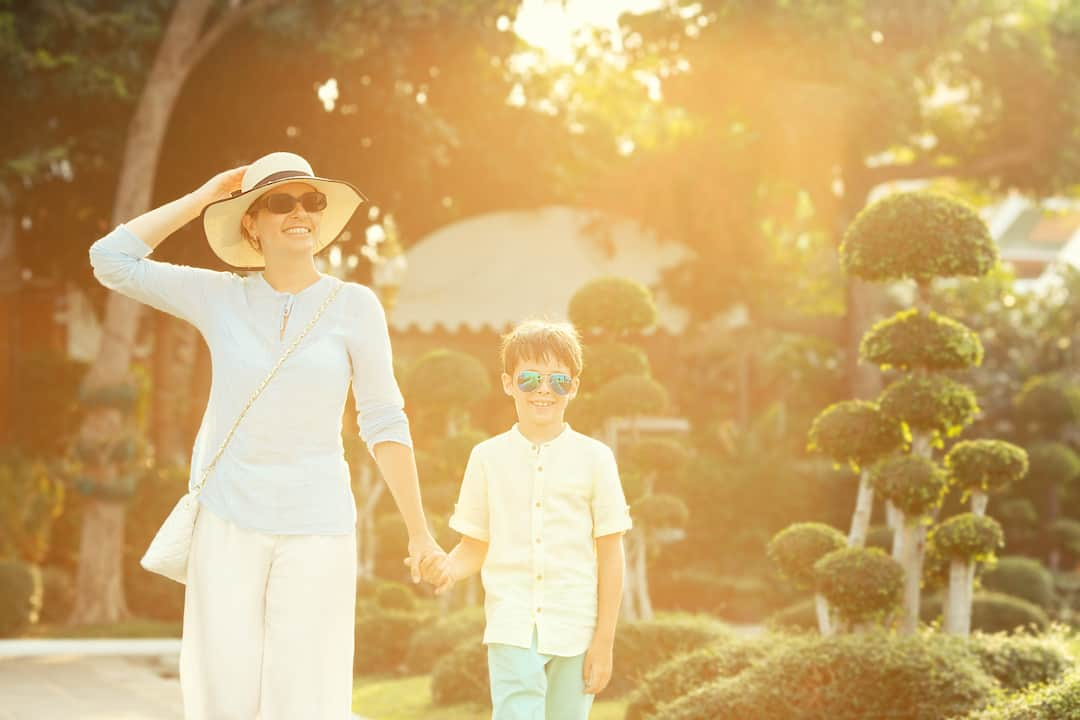 mother and son walking under the sun at mandarin oriental, bangkok