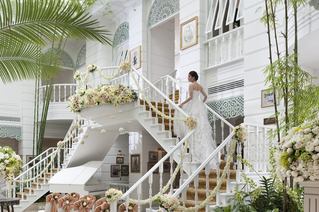 authors wing with bride on staircase at mandarin oriental, bangkok