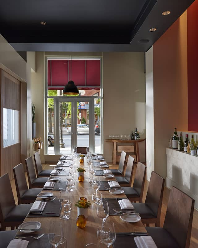 private dining area with rectangle wood table and chairs facing a glass door leading to the street