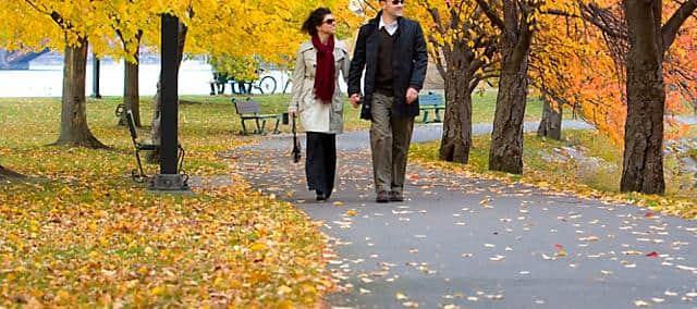 A couple wearing trench coats walking in the park in fall as tree leaves are turning yellow