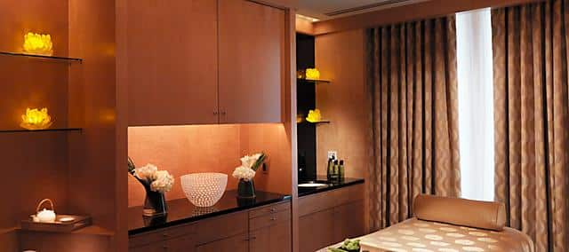 spa room designed in light brown tone with a message bed