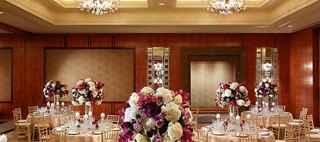 venue with round tables decorated by roses and assorted flowers