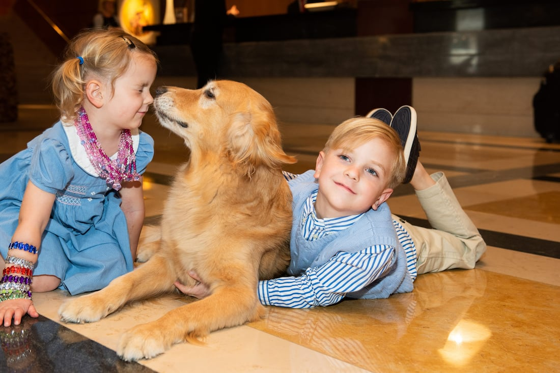 kids playing with golden retriever