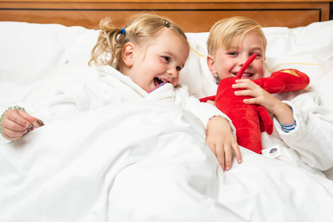 kids in bed playing with lobster doll