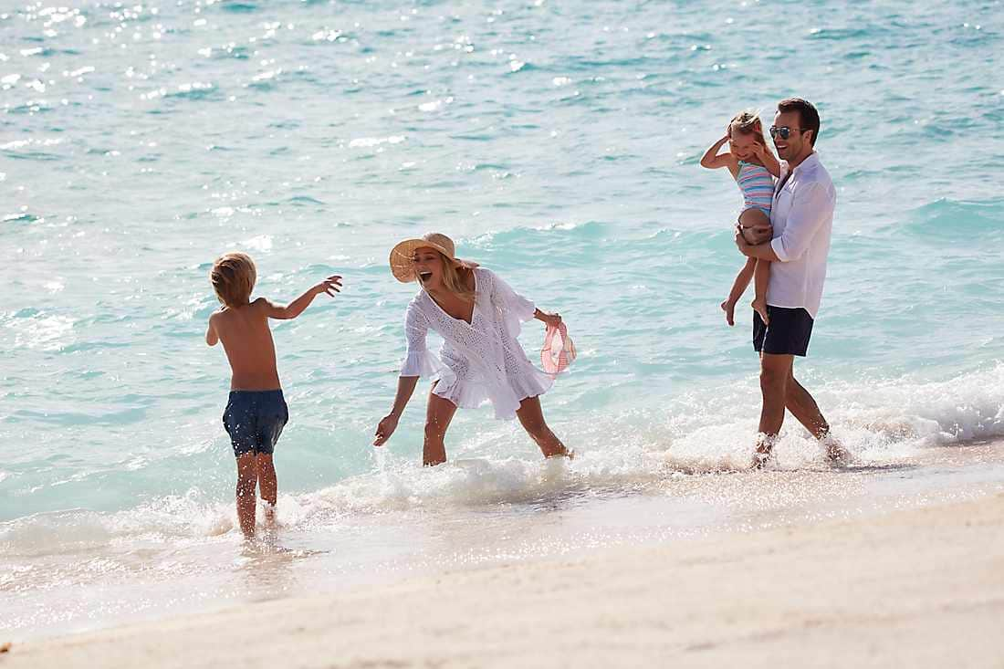 family playing in ocean