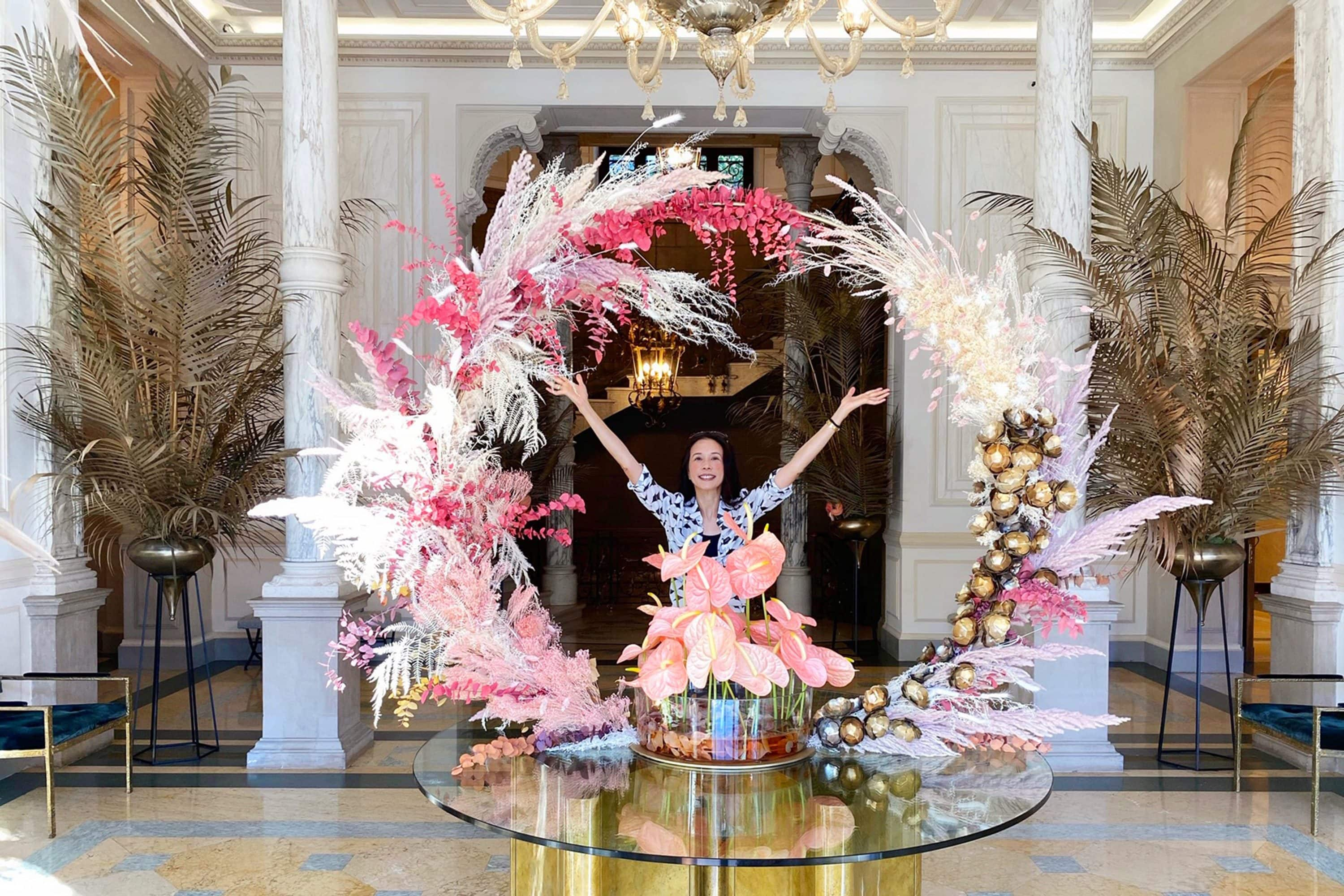 Karen Mok poses in hotel lobby surrounded by flowers
