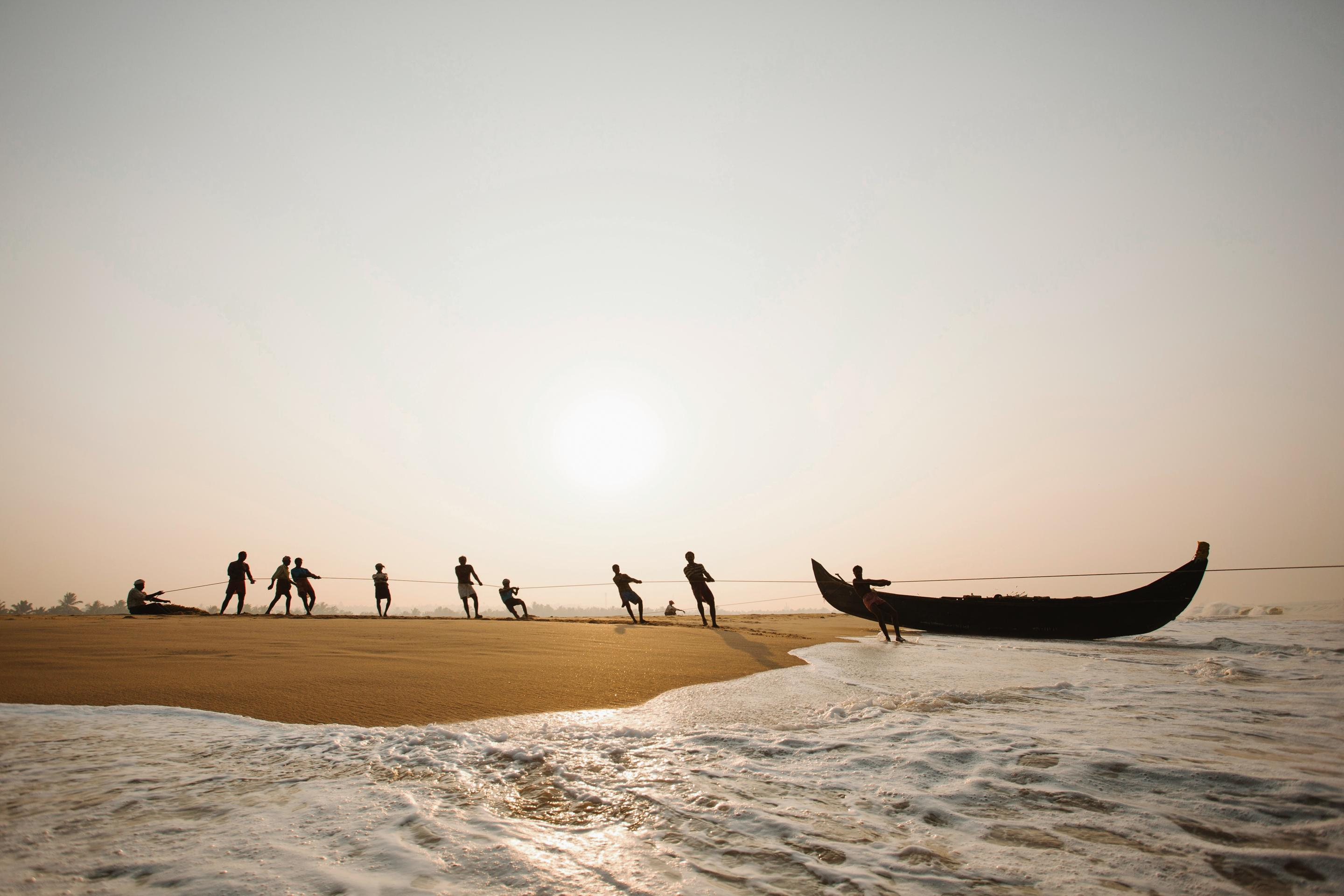 People pull long boat onto a beach at sunset