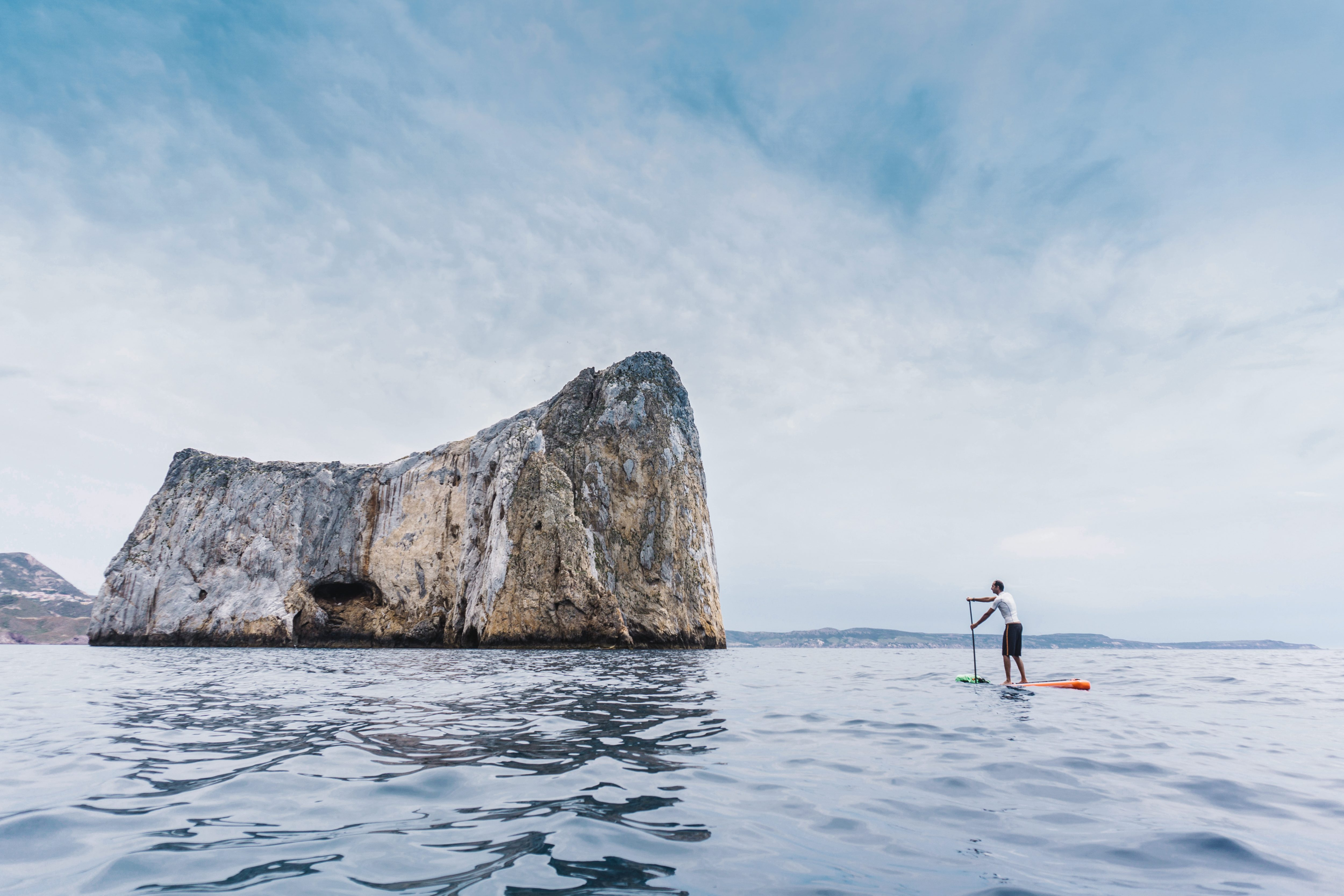 A man paddleboards on a calm sea near Sardinia