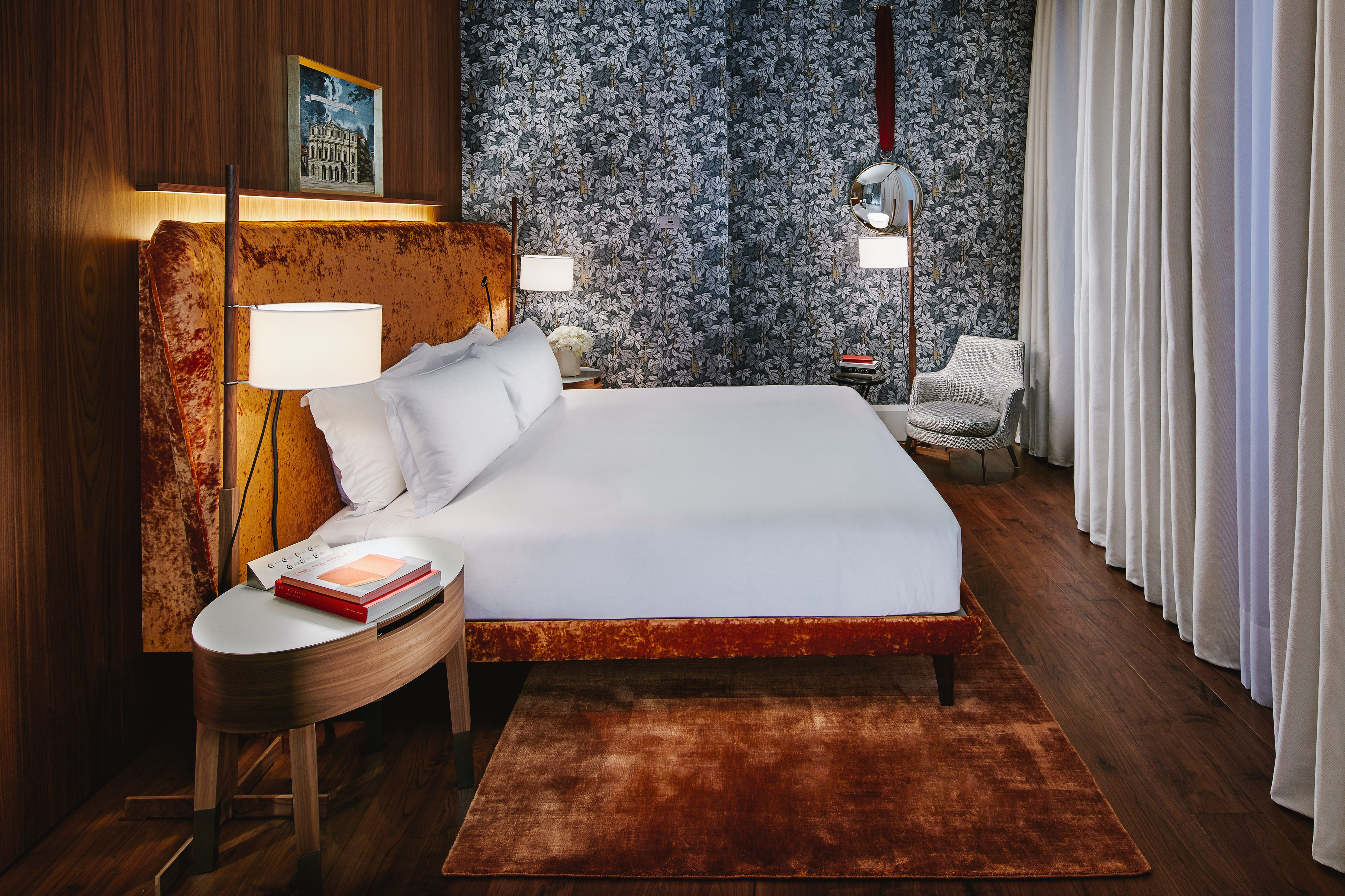 Bedroom suite at MO Milan with its crushed orange velvet headboard and floral wallpaper
