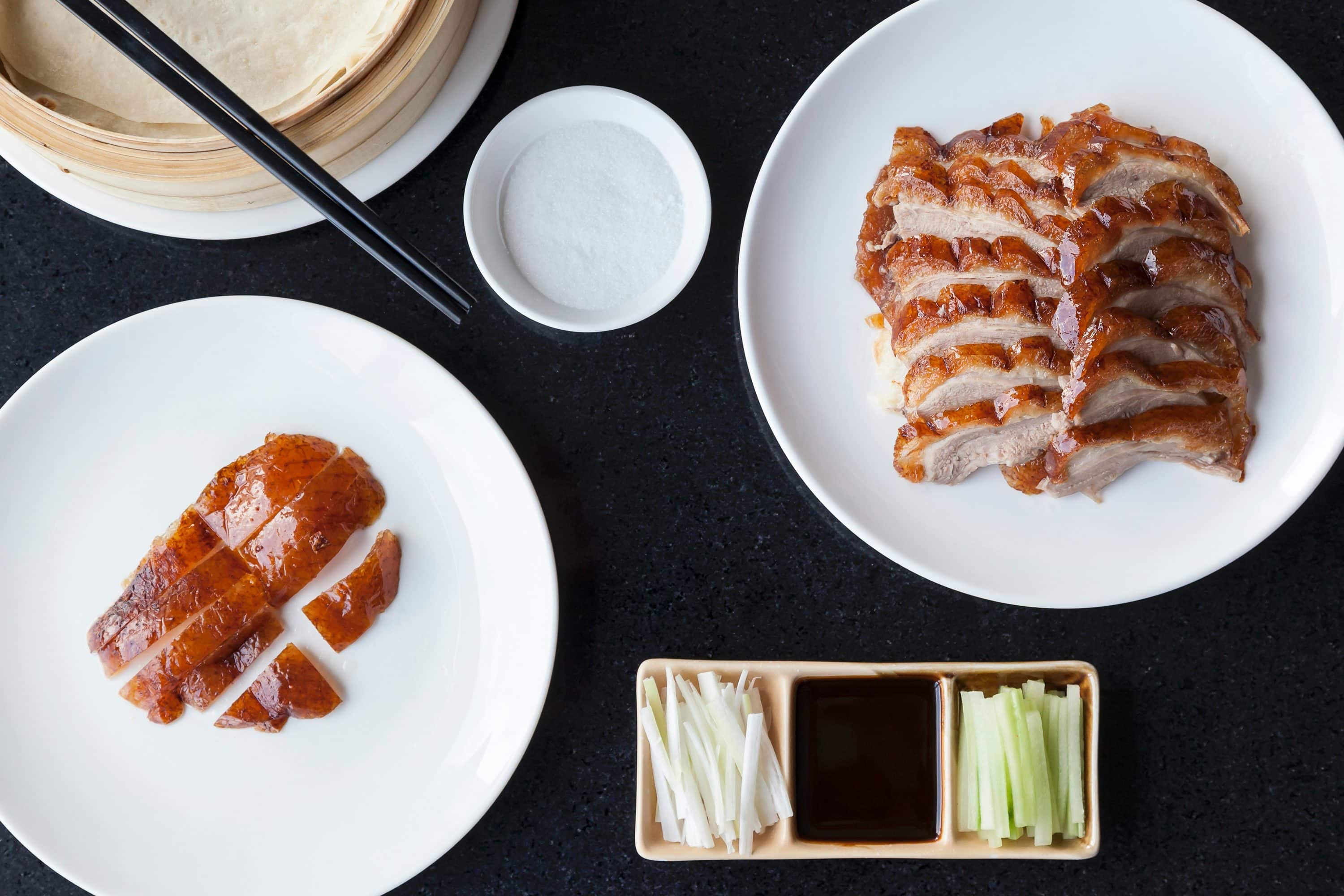 A table laid out with plates of sliced Peking duck