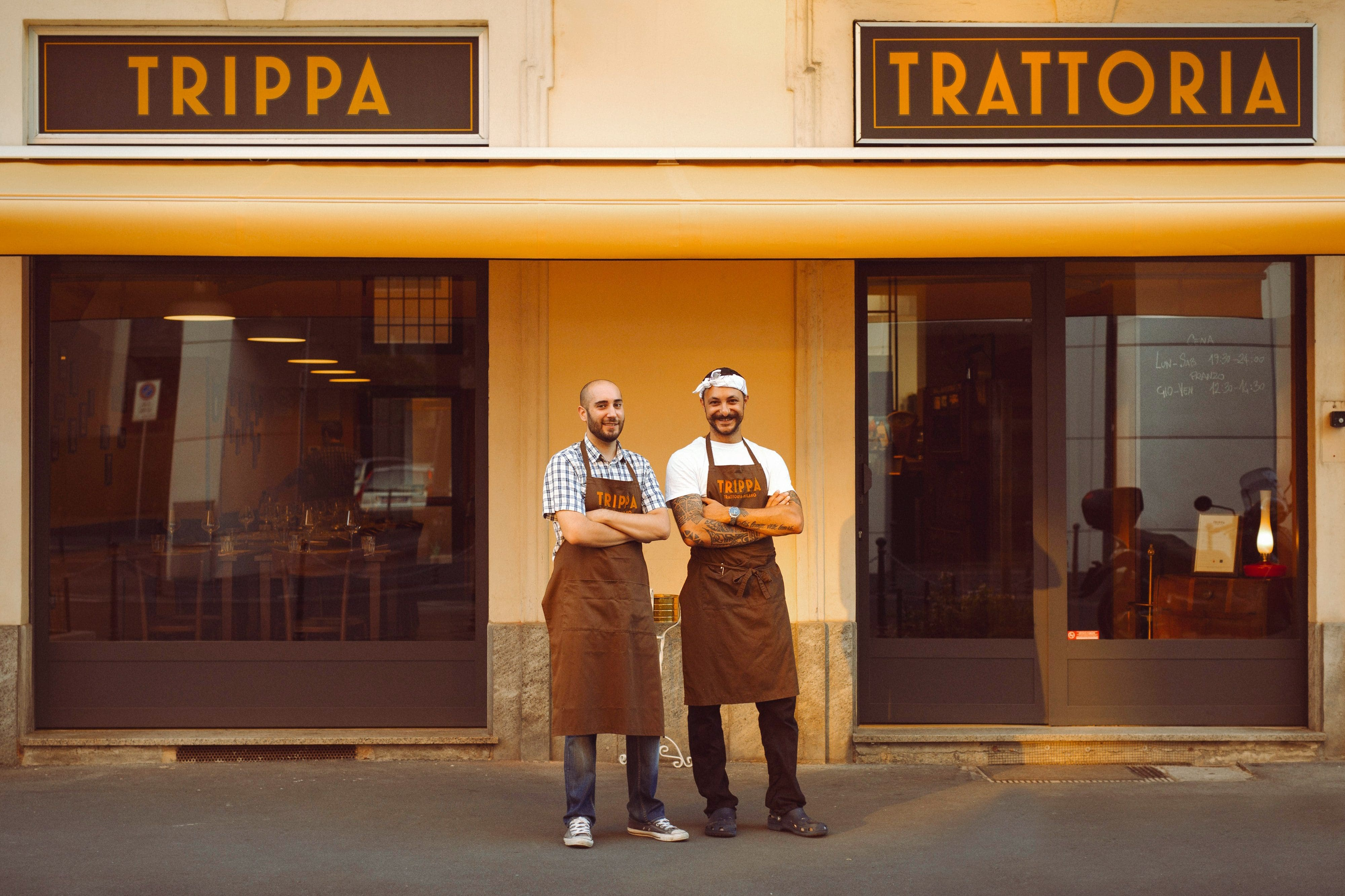 Chefs standing outside Trippa Trattoria's vintage-looking front