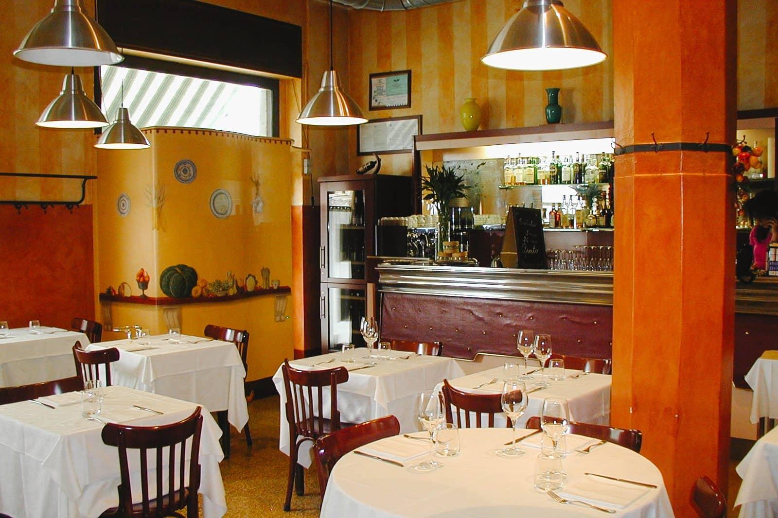 The classic orange interior and padded bar of Trattoria del Nuovo Macello