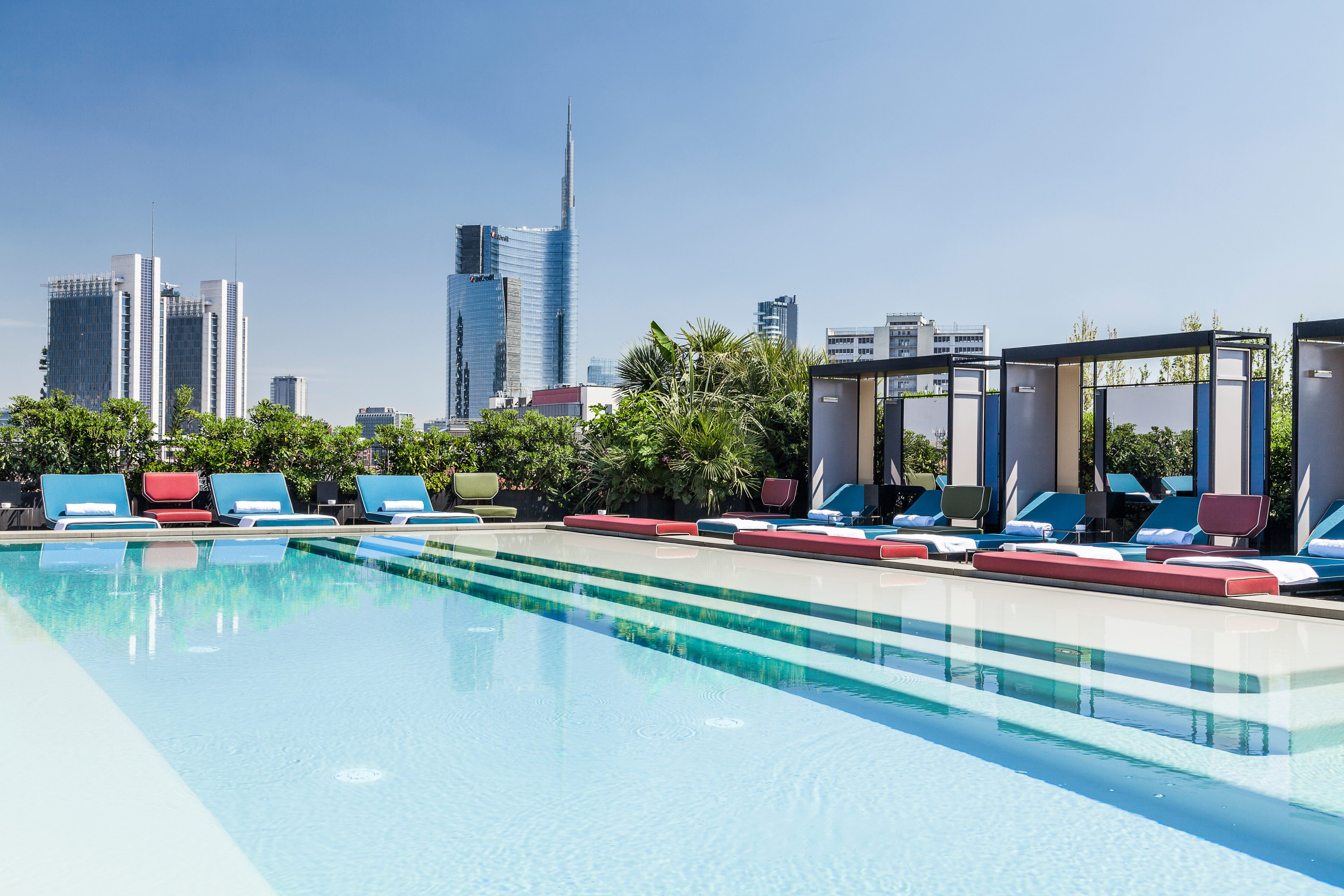 The pool and cabanas of Ceresio 7 overlooking the Milan city skyline