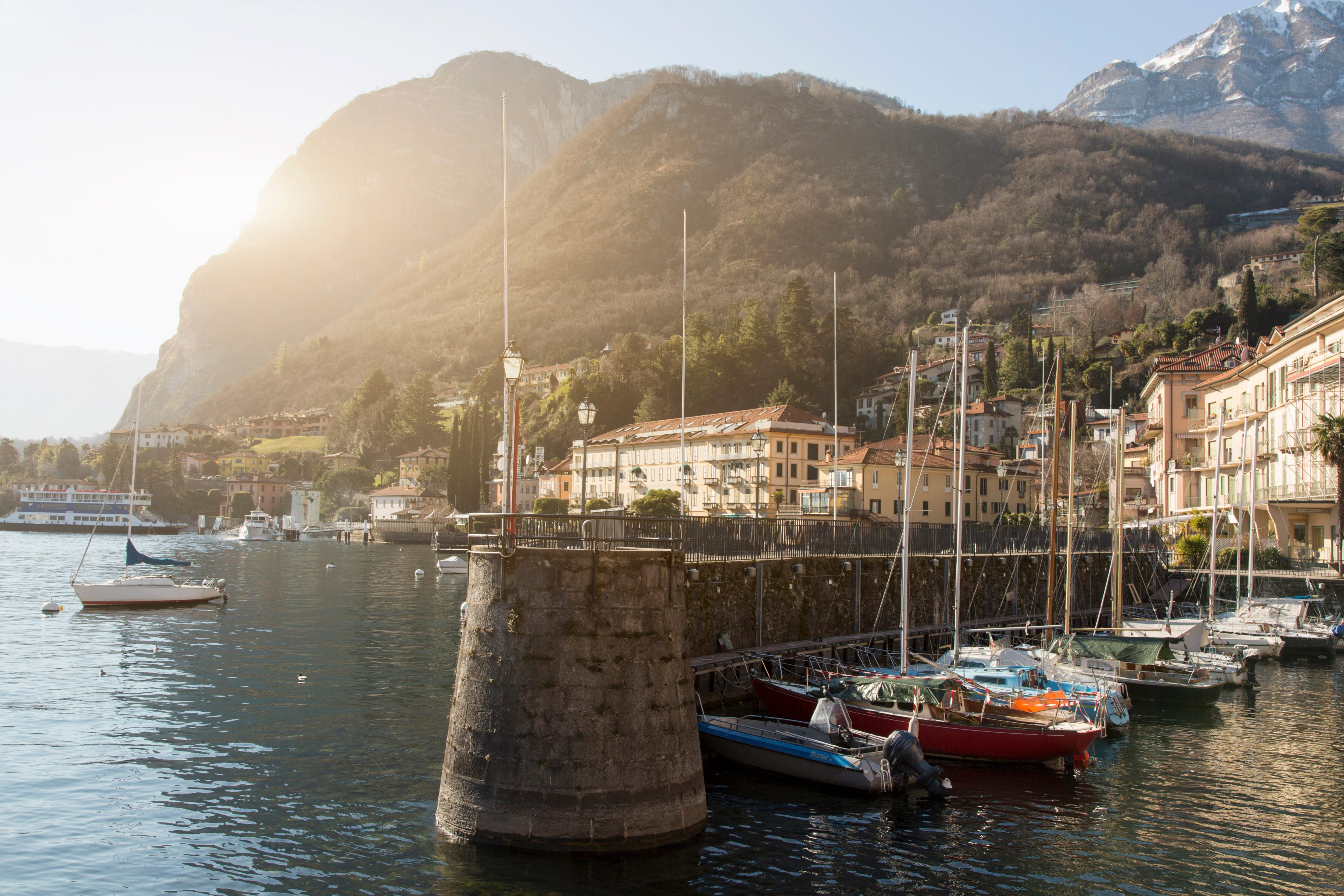 A portside at Lake Como looking from the water, with moored sailing boats and the mountain backdrop