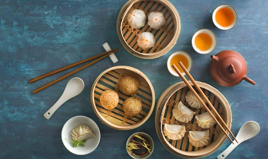 Selection of dim sum in bamboo baskets and two cups and pot of tea