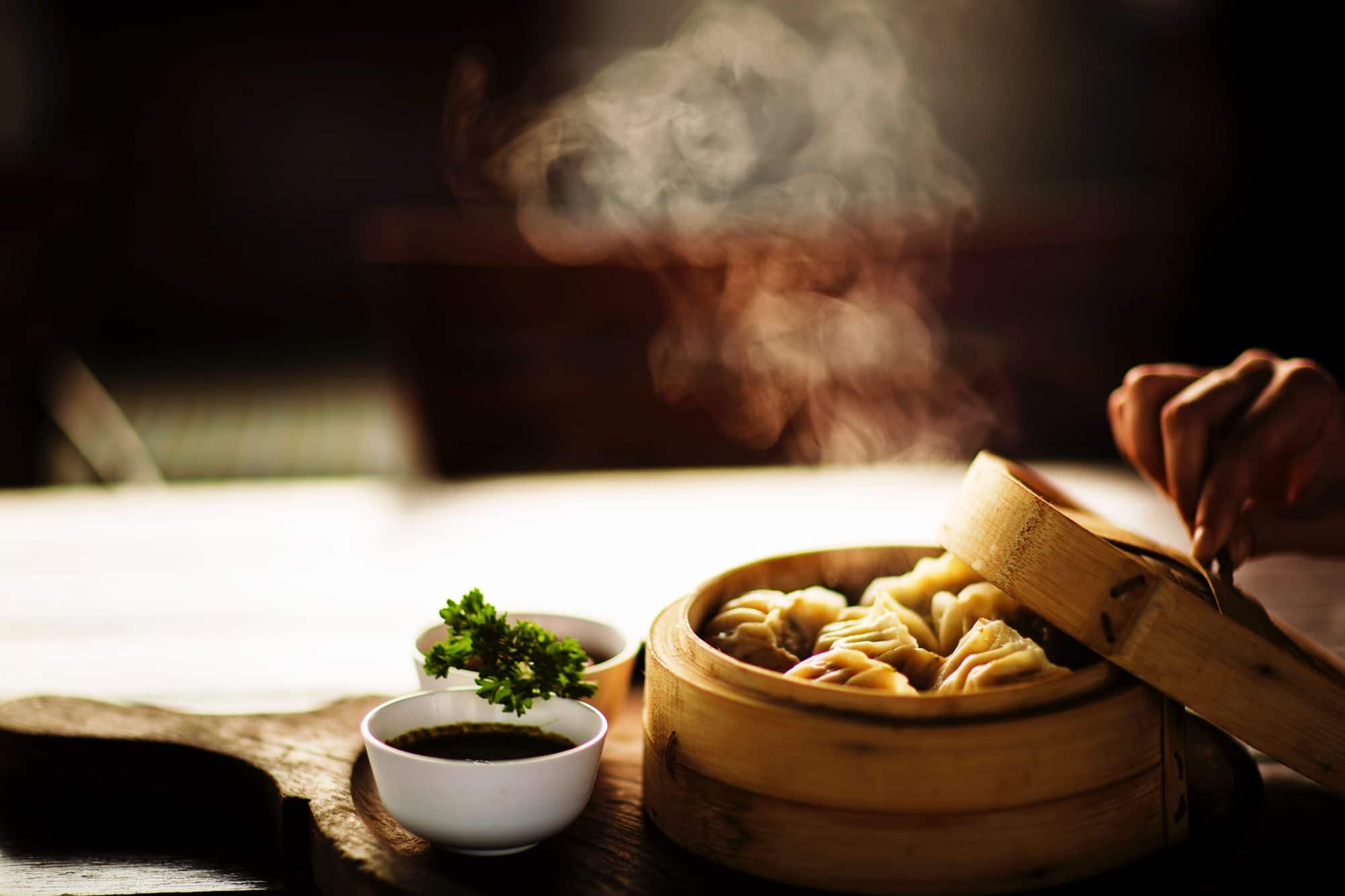 A hand opening a dim sum steamer to reveal dumplings, and dipping sauces by the side