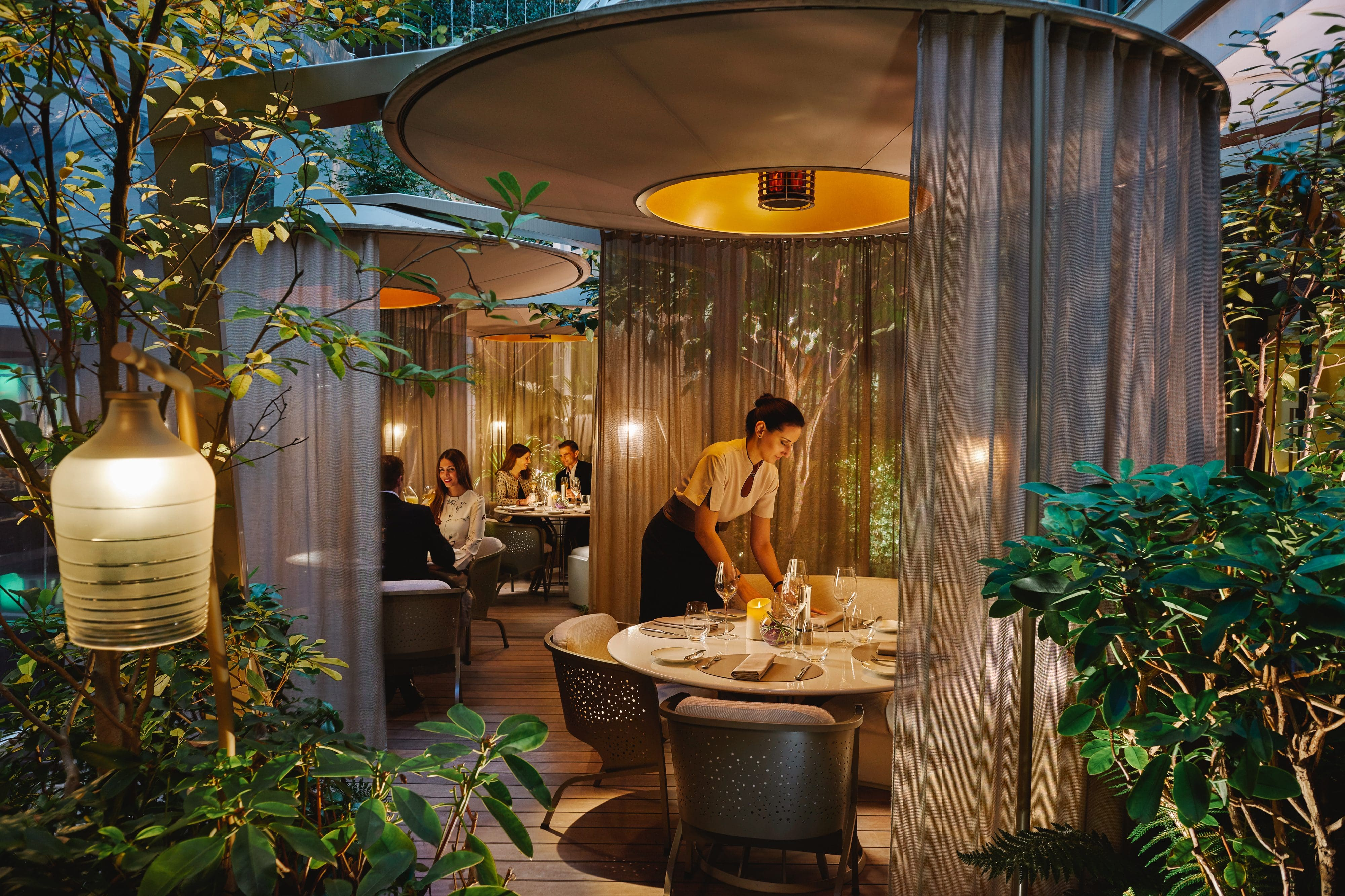 People dining in the indoor-outdoor 'pods' at Camilia at Mandarin Oriental, Paris