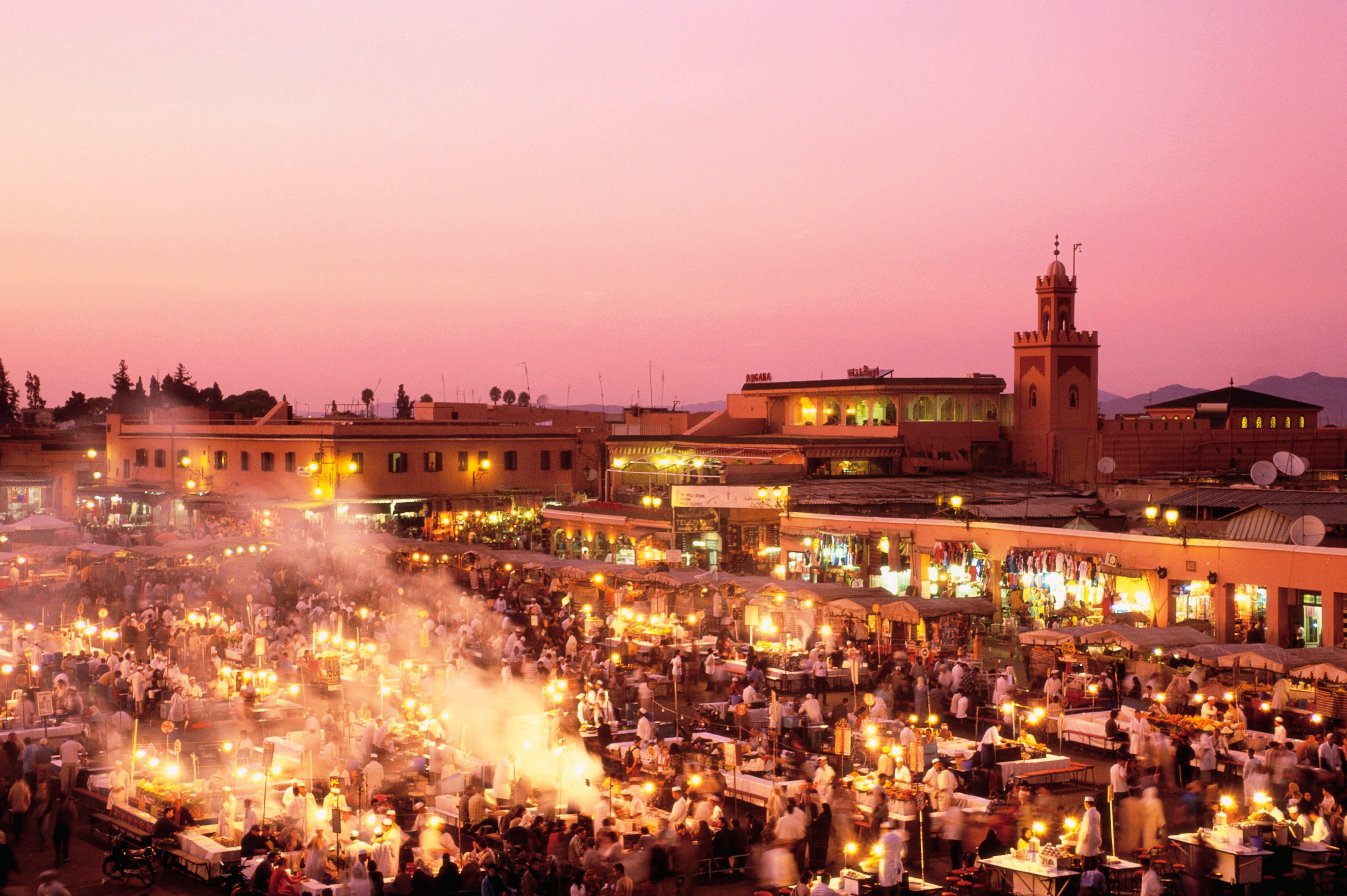 The illuminated Medina marketplace in Marrakech under a coral-hued sky