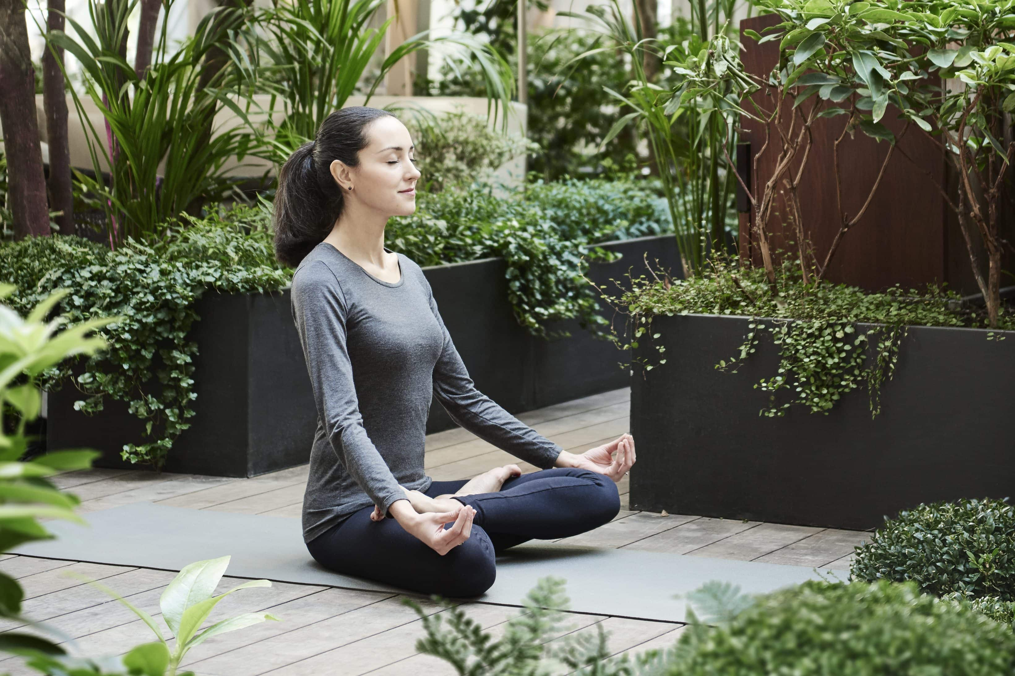 Woman practising yoga in the garden at Mandarin Oriental, Paris