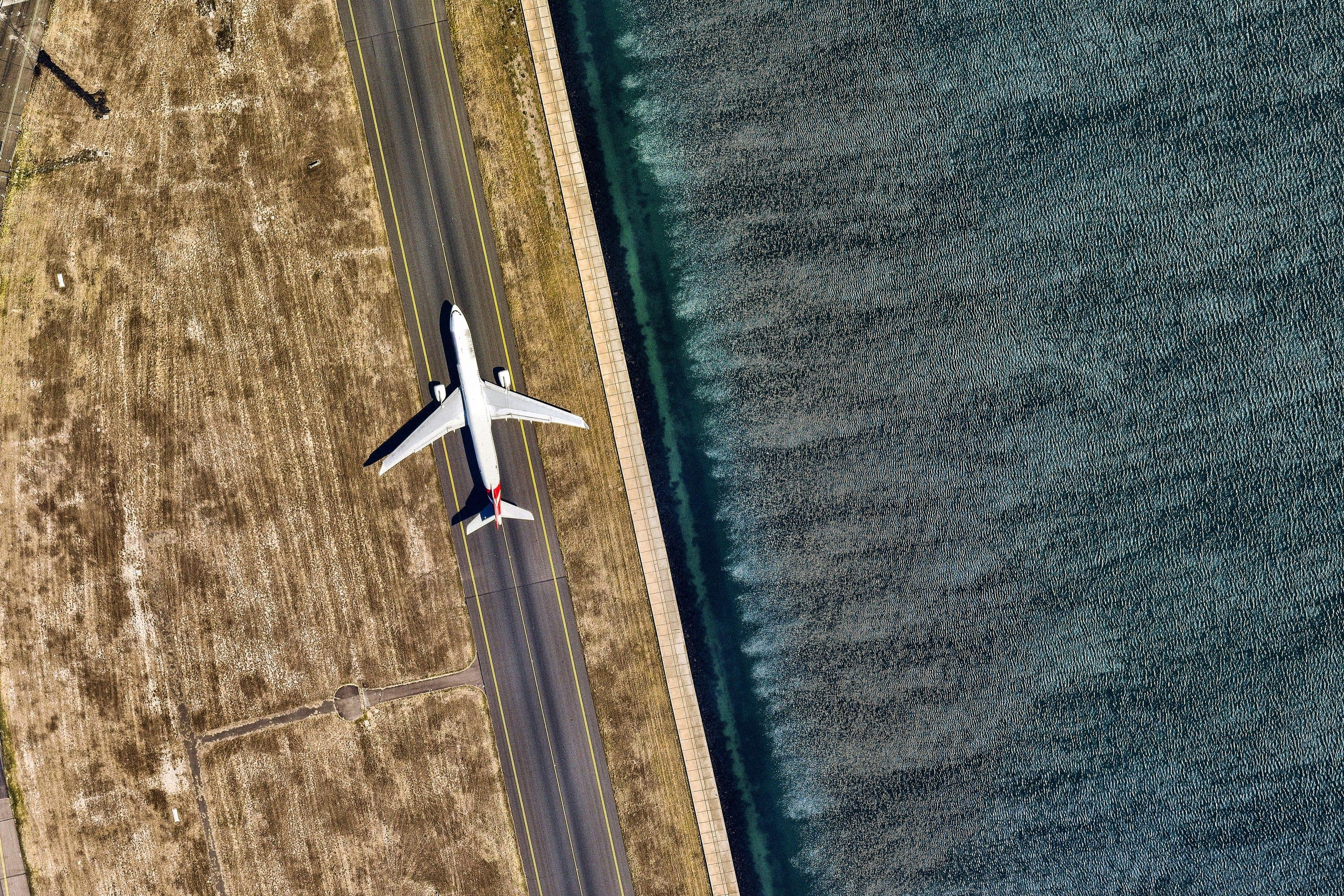 Bird's-eye view of a plane moving along a runway next to the ocean