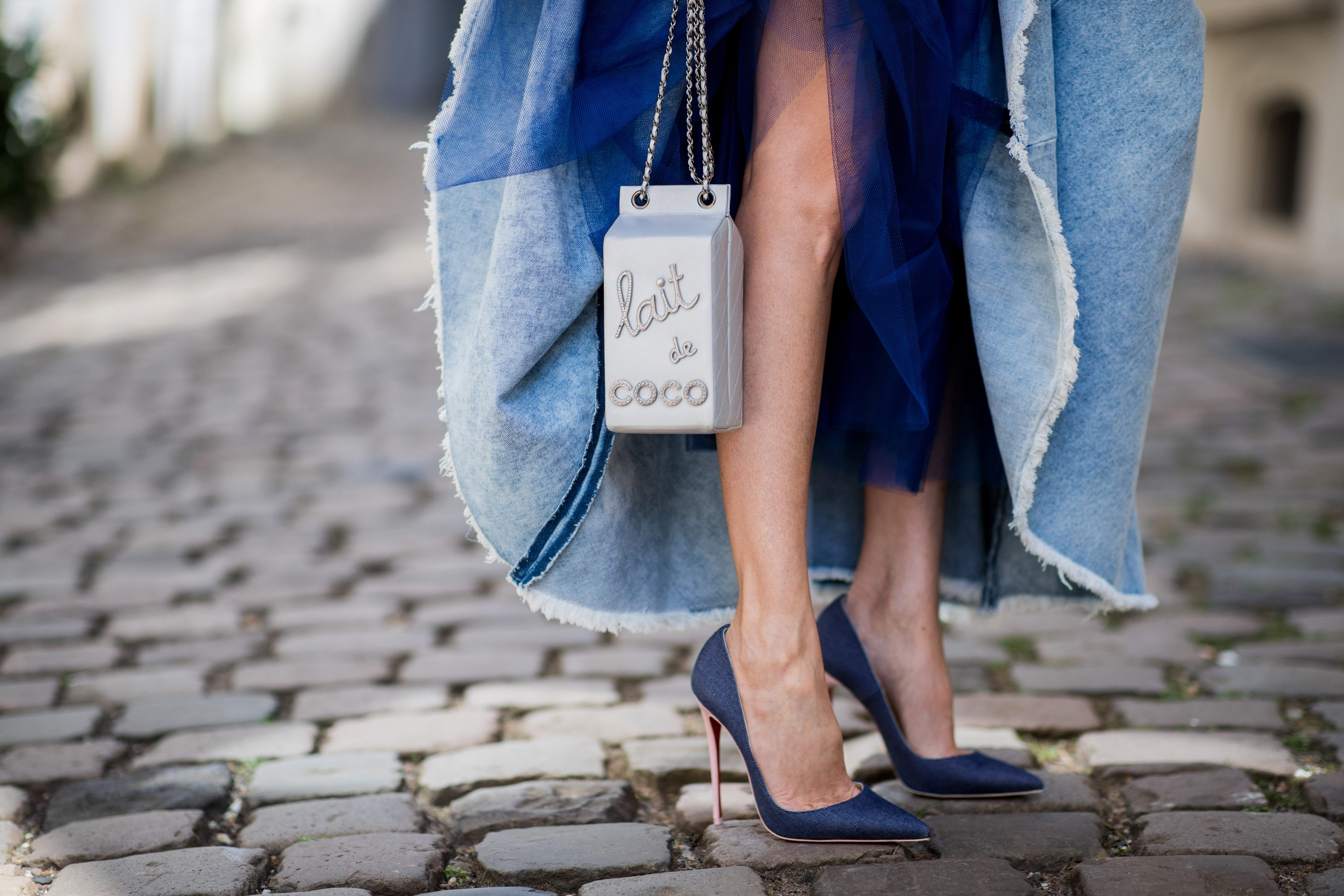 "A woman standing on a cobblestone street, wearing blue Louboutin high heels and a blue coat with a ""Lait de Coco"" handbag"