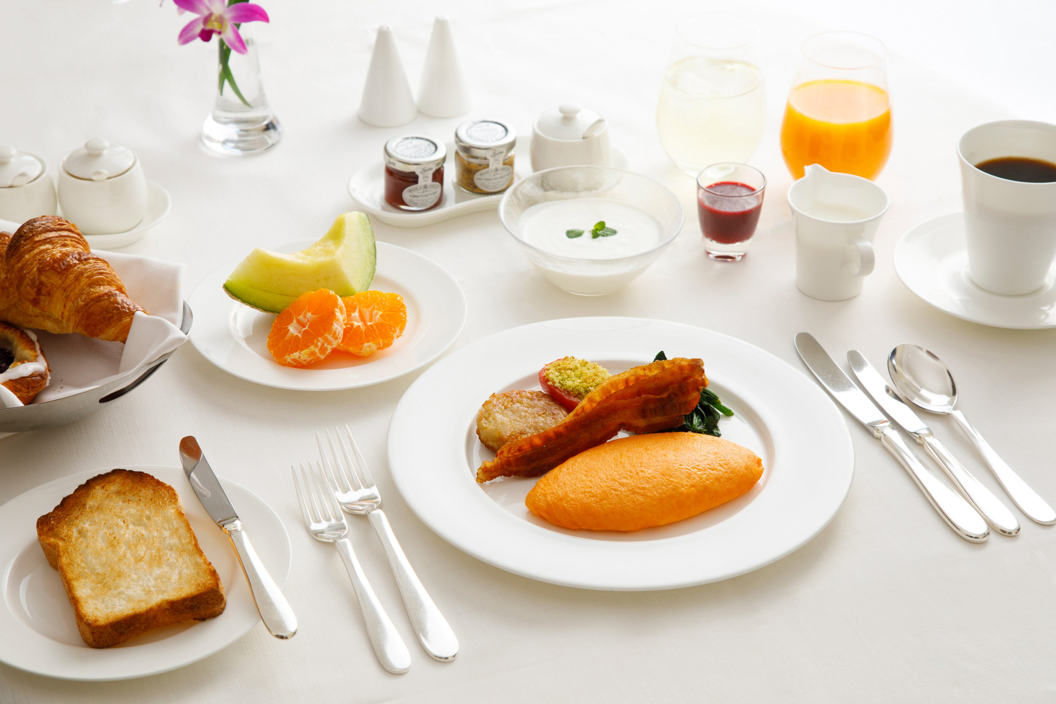 A breakfast table with orange juice, coffee, fresh fruit and toast