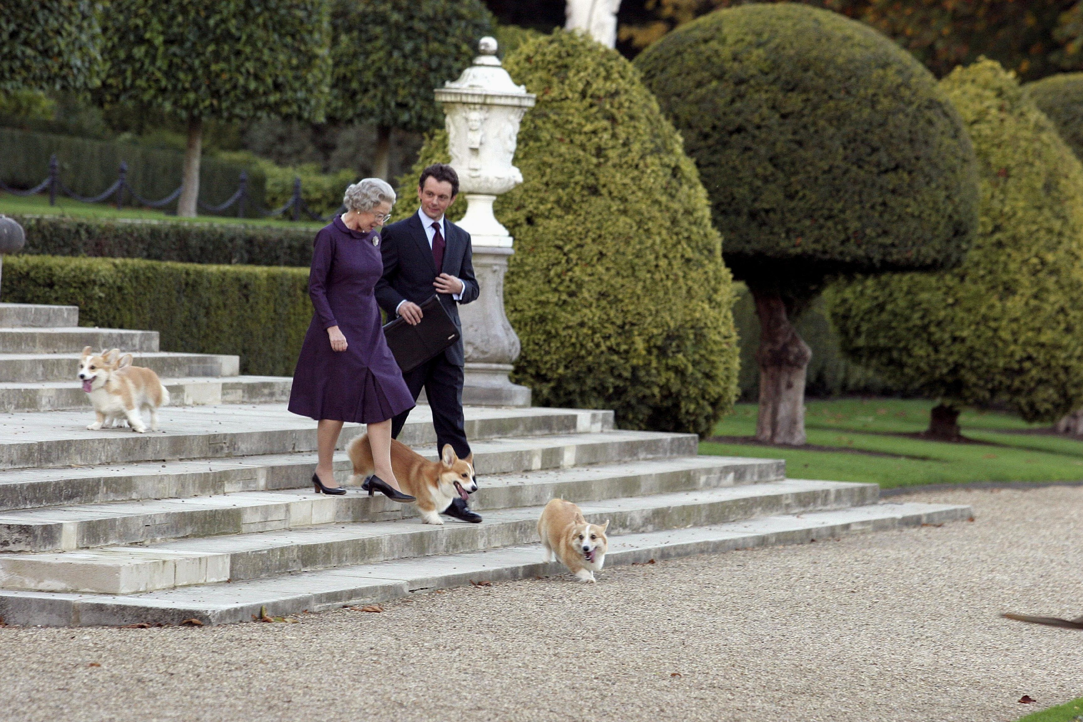 Dame Helen Mirren with Michael Sheen with corgis and a garden as part of the filming for The Queen
