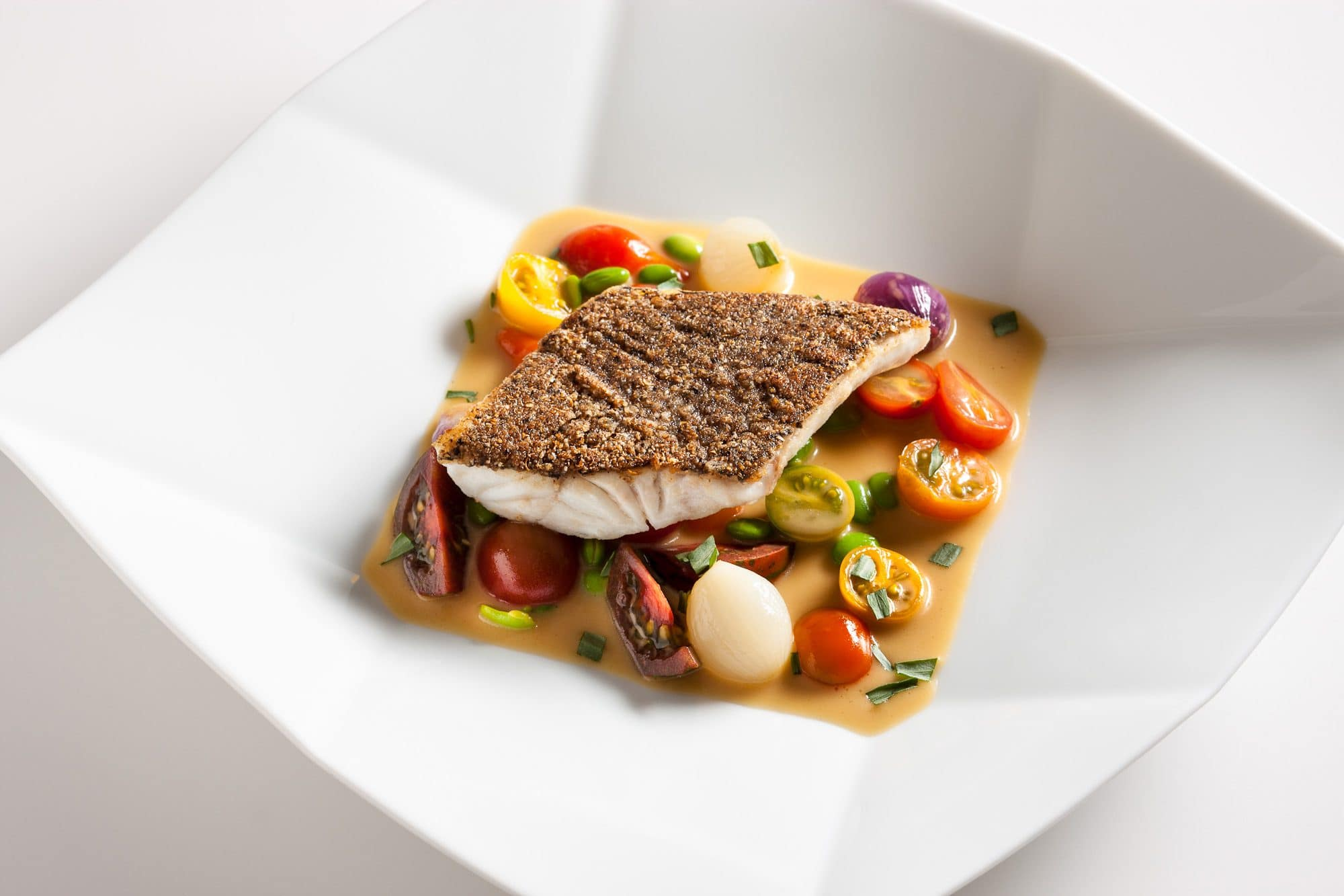 A fish dish with pan-fried fish and tomatoes