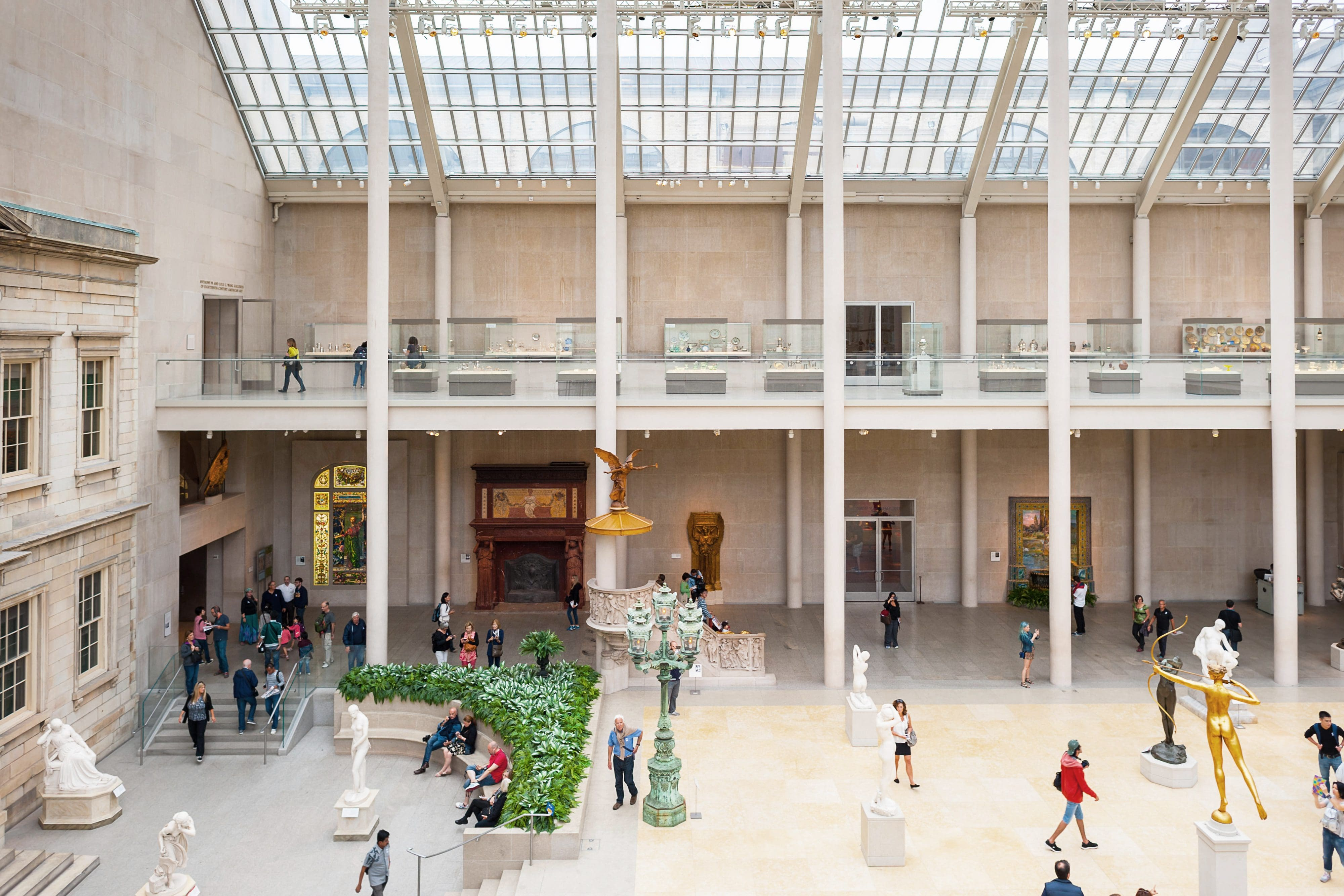 Overhead shot of the The American Wing conservatory showing people studying the art and sculptures