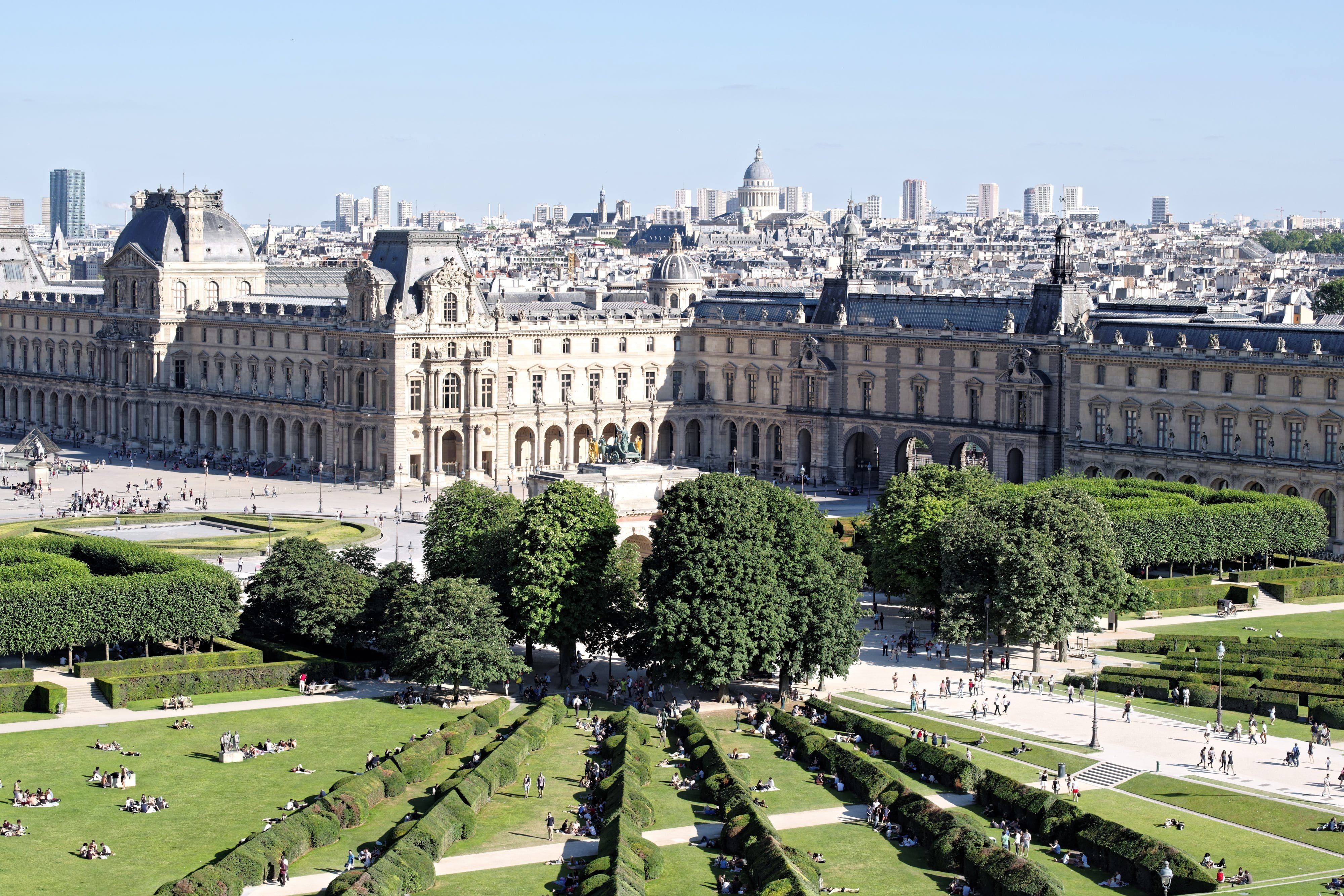 Beautiful fan-patterned gardens with green shrubs in front of the beautiful stone buildings of Tuileries Garden