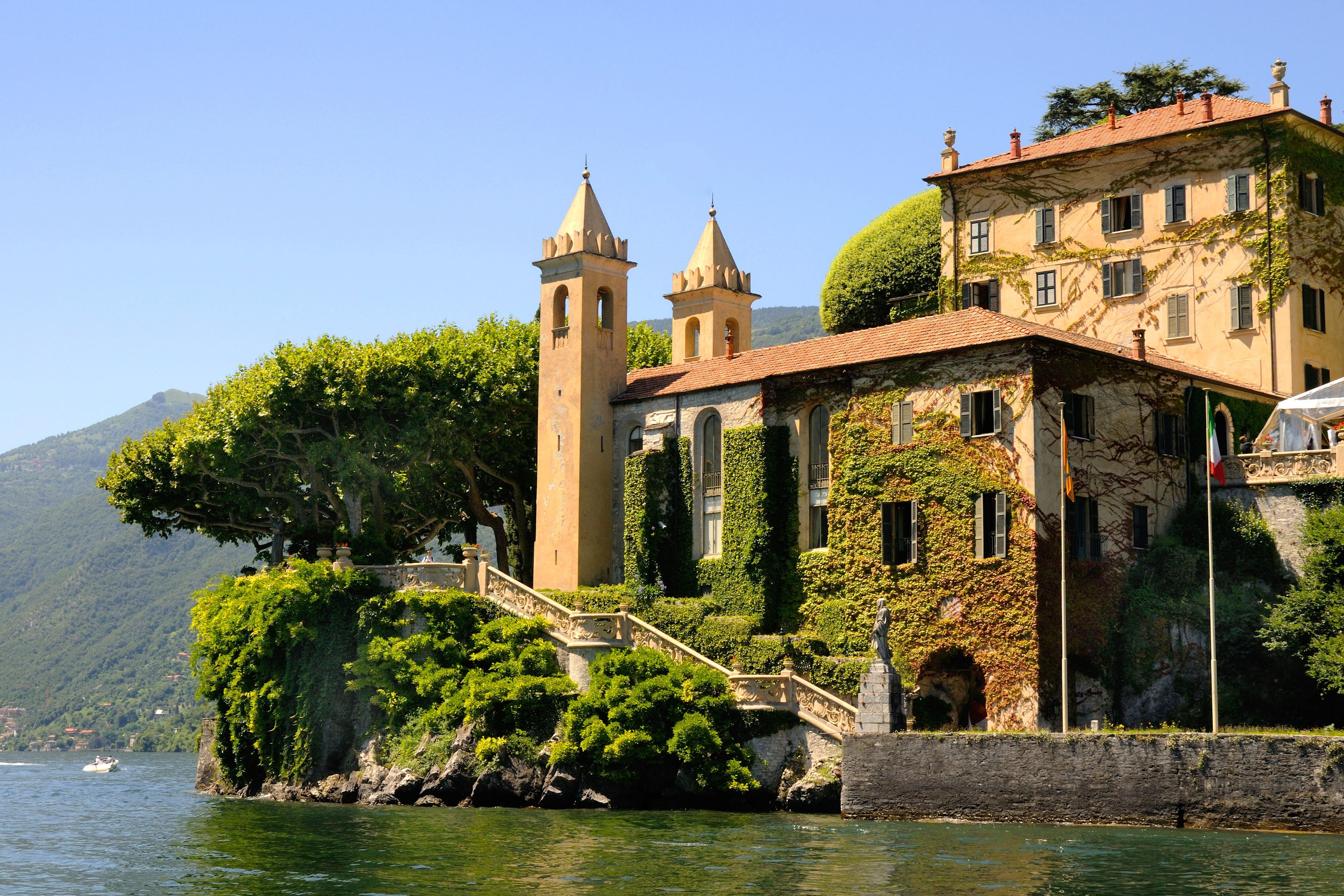 The ivy-covered walls of Villa del Balbianello with its turrets on the headland on the banks of Lake Como