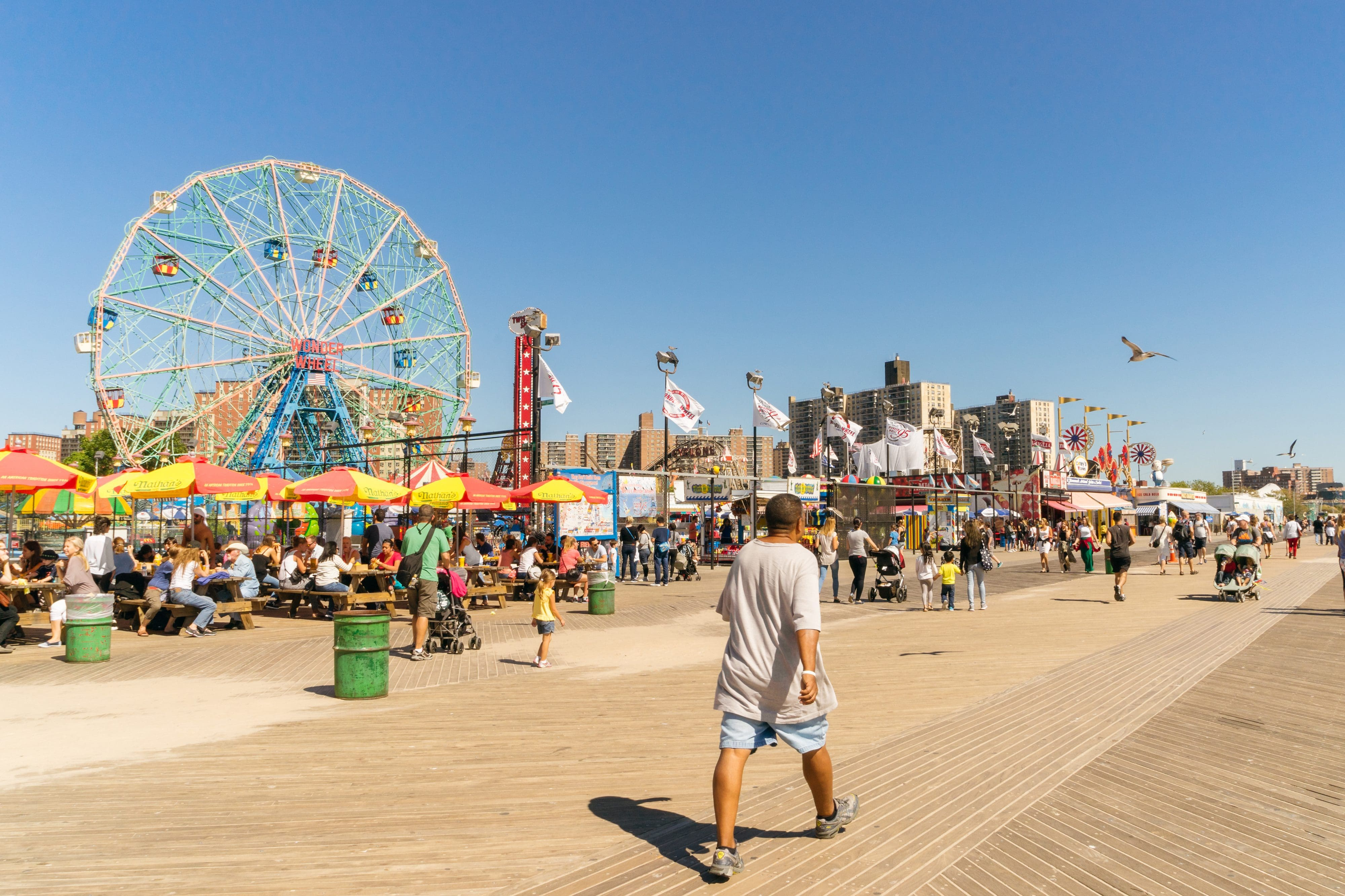 The colourful boardwalk of Coney Island with the famous Ferris wheel in the background