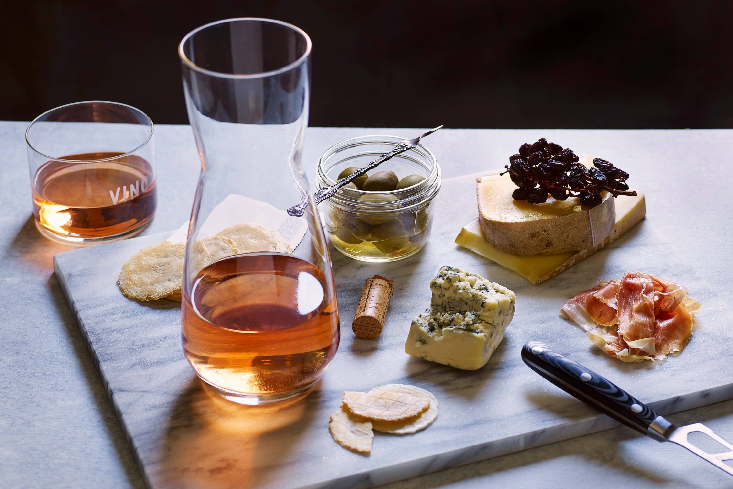 Cheese board with a decanter of rose wine