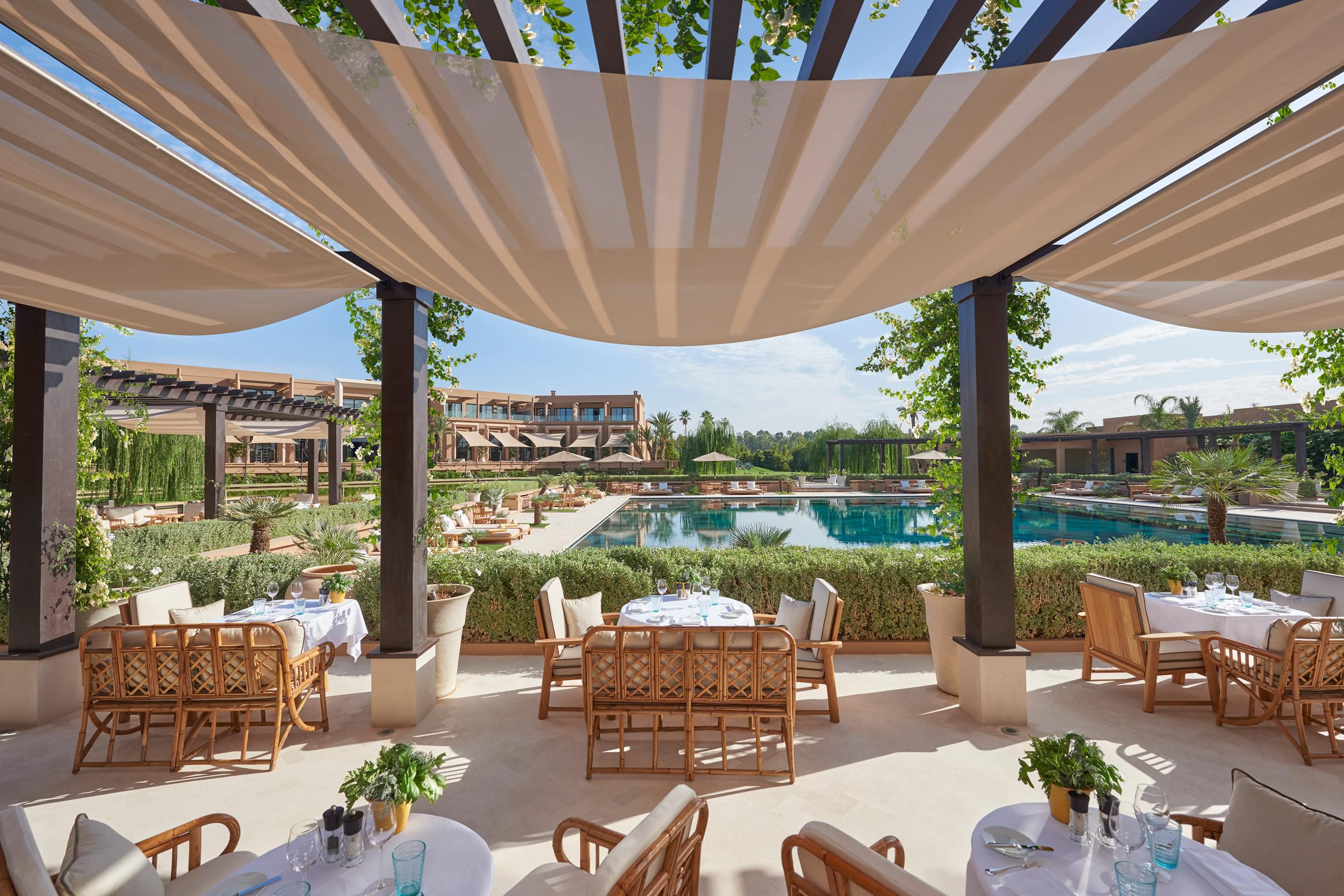 Tables and sun loungers surround the pool at Mandarin Oriental, Marrakech