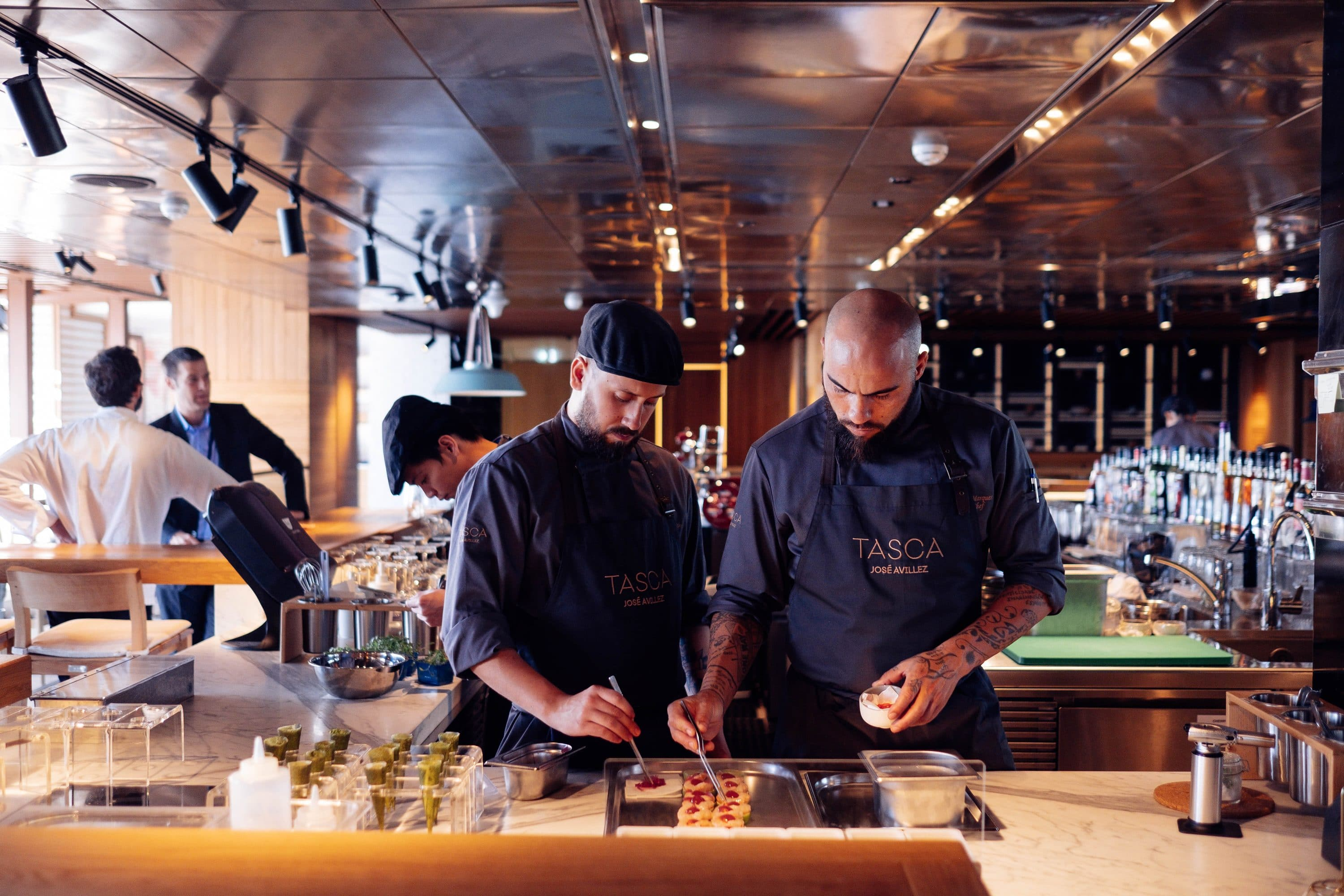 Chefs adding the finishing flourishes to dishes in the open kitchen of Tasca restaurant